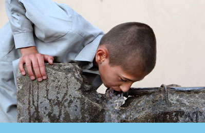 Photo of Afghan boy drinking from water fountain